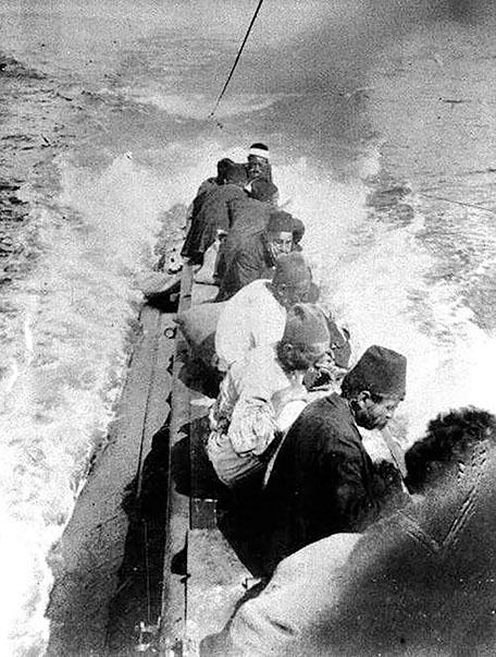 Batırılan bir Türk gemisinin mürettabatı E-11 denizaltısının güvertesinde kıyıya taşınıyor